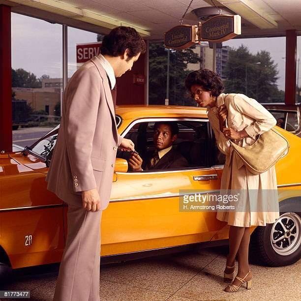 african-american couple buy new orange car from a salesman at automobile dealer showroom. - 1970年 ストックフォトと画像
