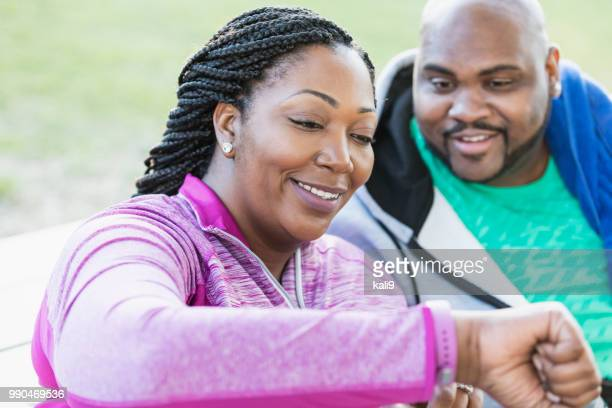 african-american couple, checking fitness tracker - fitness tracker stock pictures, royalty-free photos & images