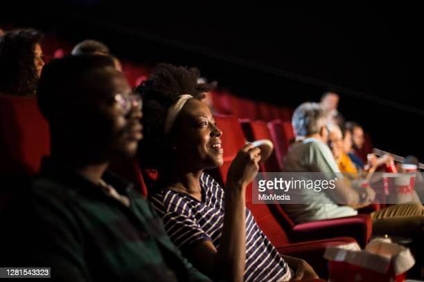 african-american couple enjoying at the cinema - film industry stock pictures, royalty-free photos & images