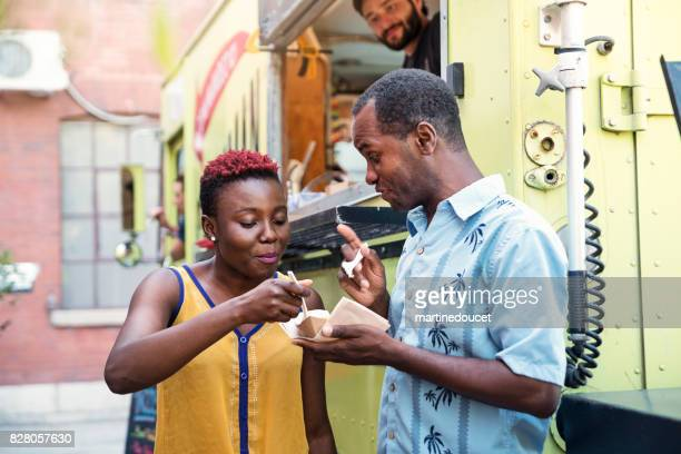 "african-american couple enjoying their lunch from food truck in city street. - ""martine doucet"" or martinedoucet stock pictures, royalty-free photos & images"