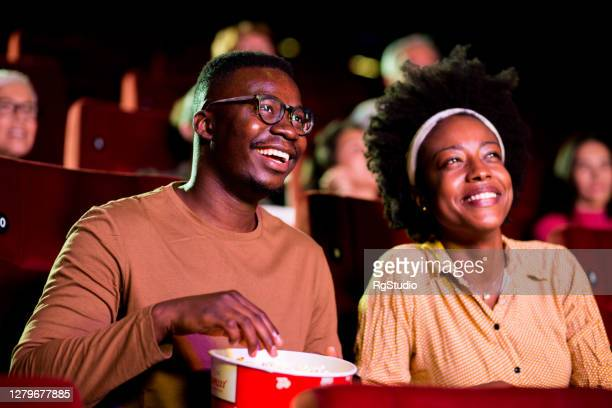 african-american couple enjoying while watching a fun movie at the cinema - film industry stock pictures, royalty-free photos & images