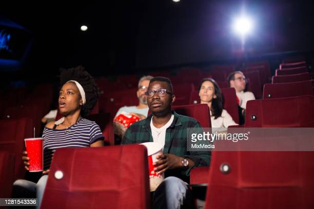 african-american couple in the cinema watching a horror movie - film premiere stock pictures, royalty-free photos & images