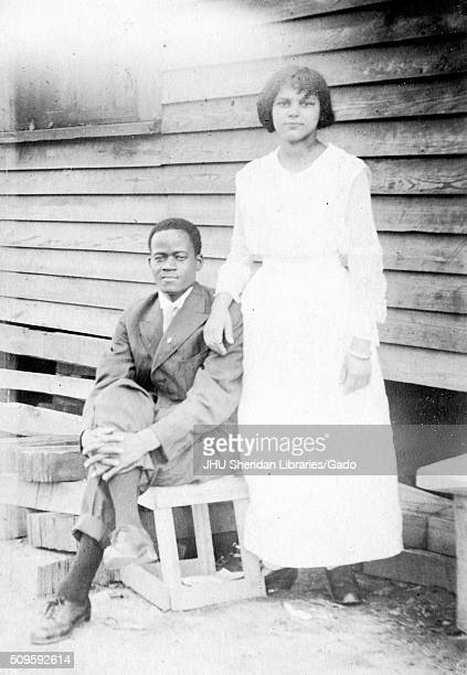 AfricanAmerican couple posing in front of a house with wood siding wife wearing white dress and standing husband sitting on a wooden crate with his...
