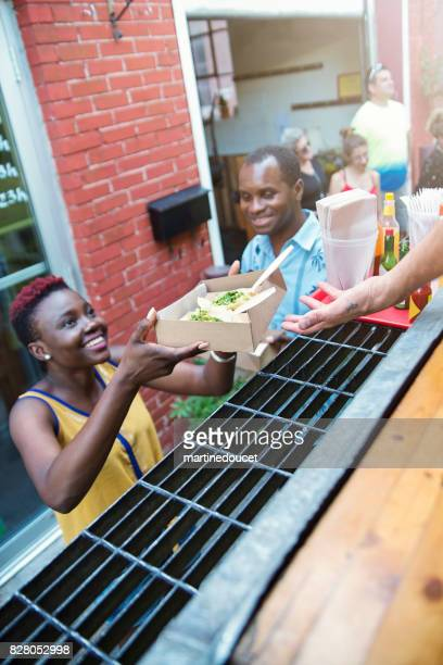 """african-american couple taking out lunch from food truck. - """"martine doucet"""" or martinedoucet stock pictures, royalty-free photos & images"""