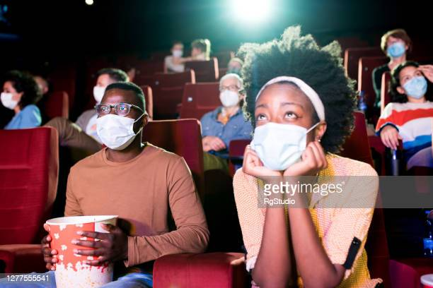 african-american couple watching a movie at the cinema during covid-19 pandemic - girlfriends films stock pictures, royalty-free photos & images