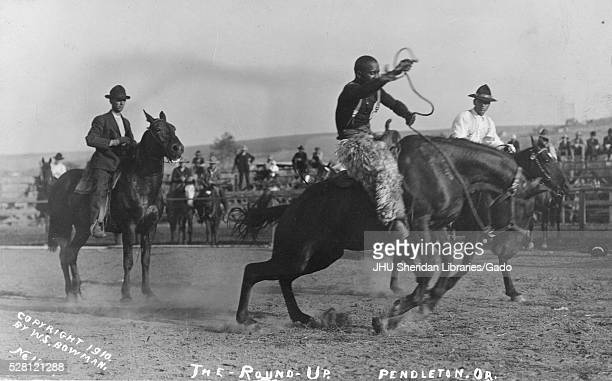 AfricanAmerican cowboys riding horses in a rodeo area with spectators and other participants in the background at the first annual Pendleton RoundUp...