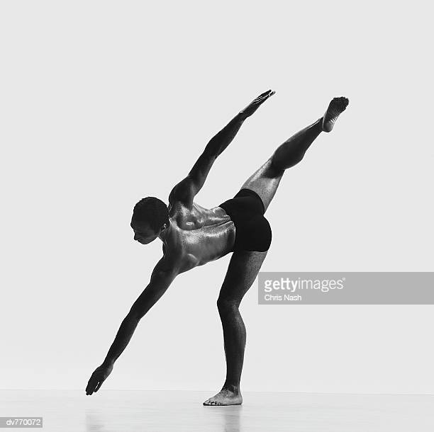 african-american dancer standing on one leg and reaching the floor with his outstretched arm - man bending over from behind stock photos and pictures