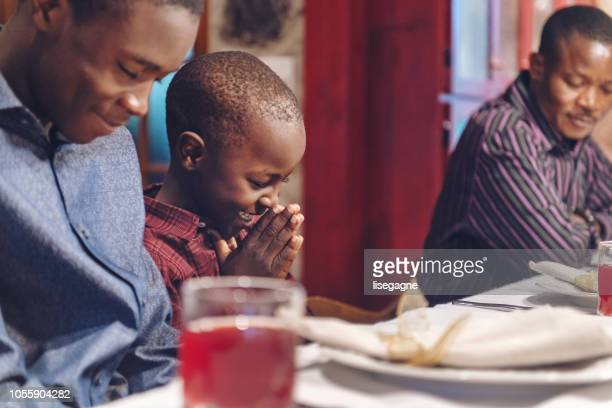 african-american doing prayer during thanksgiving dinner - praying stock pictures, royalty-free photos & images