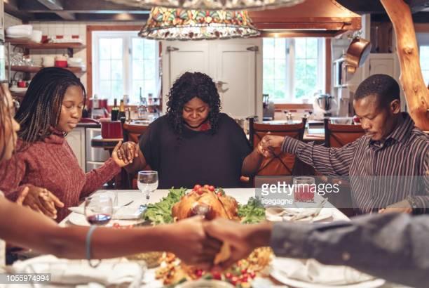africano-americano a fazer oração durante o jantar de ação de graças - african american family dinner - fotografias e filmes do acervo