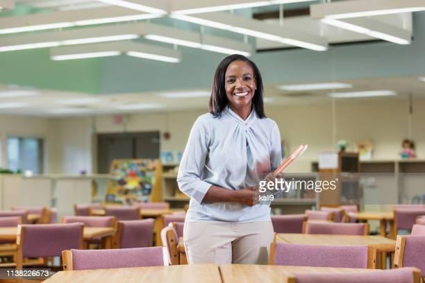 professeur d'école élémentaire afro-américaine dans la bibliothèque - enseignante photos et images de collection