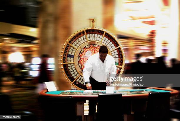 African-American employee in front of wheel of fortune in casino
