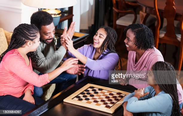 african-american family at home playing checkers - chequers stock pictures, royalty-free photos & images