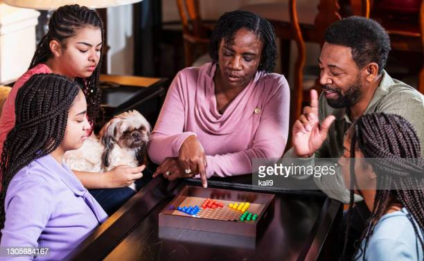 african-american family at home playing chinese checkers - chequers stock pictures, royalty-free photos & images