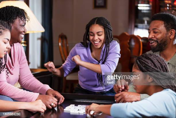 african-american family at home playing dominoes - game night leisure activity stock pictures, royalty-free photos & images