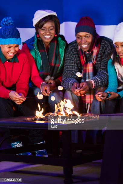 アフリカ系アメリカ人家族は、火災のピットの焙煎マシュマロ