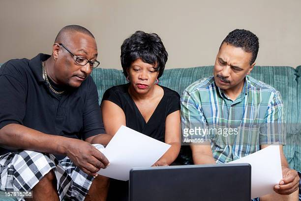 african-american family looking at the papers in their home - alina stock pictures, royalty-free photos & images