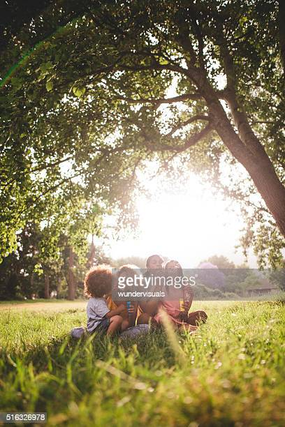 African-american family sitting in beautiful park blowing bubble