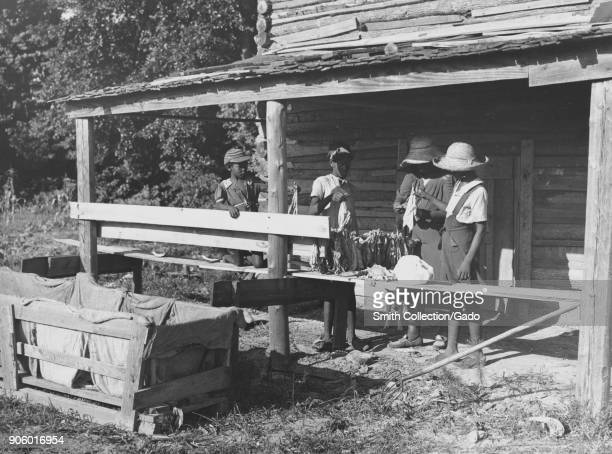 AfricanAmerican family working at tobacco harvest on porch of wooden hut Clarendon County South Carolina USA 1940 From the New York Public Library