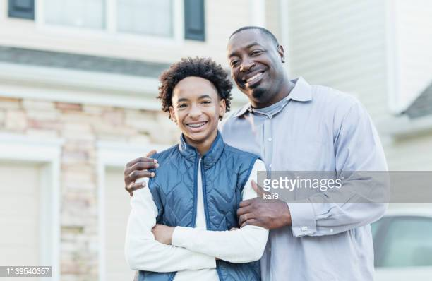 african-american father, mixed race son in front of home - brace stock pictures, royalty-free photos & images