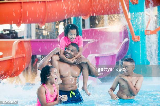 African-American father, three children at water park