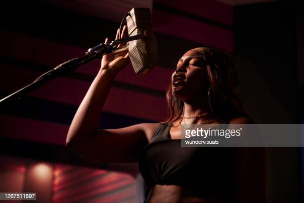 african-american female artist singing on microphone in music studio recording booth - rapper stock pictures, royalty-free photos & images