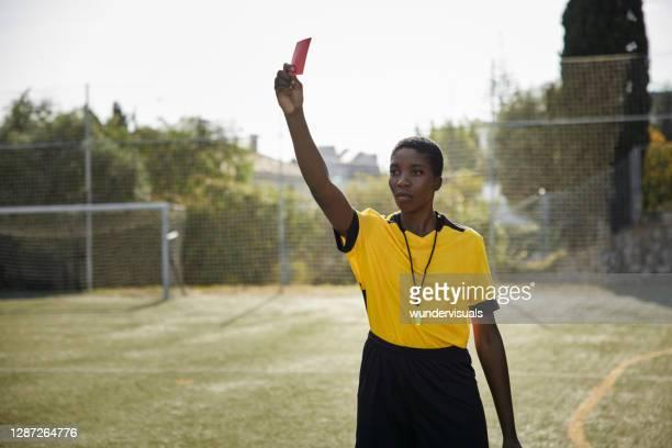 arbitro mujer afroamericana sosteniendo tarjeta roja en uniforme amarillo - árbitro deportes fotografías e imágenes de stock