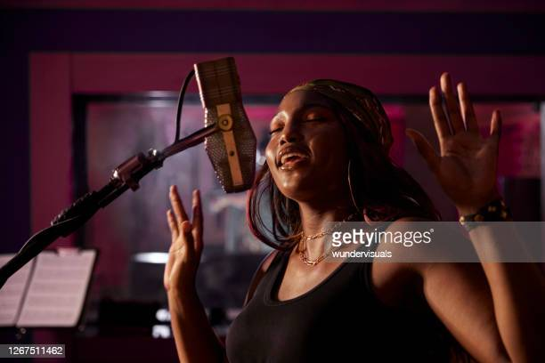 african-american female singer recording vocals on microphone in music studio recording booth - songwriter stock pictures, royalty-free photos & images