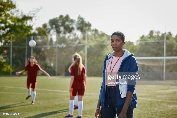 african-american female soccer coach standing in soccer team practice - manager stock pictures, royalty-free photos & images
