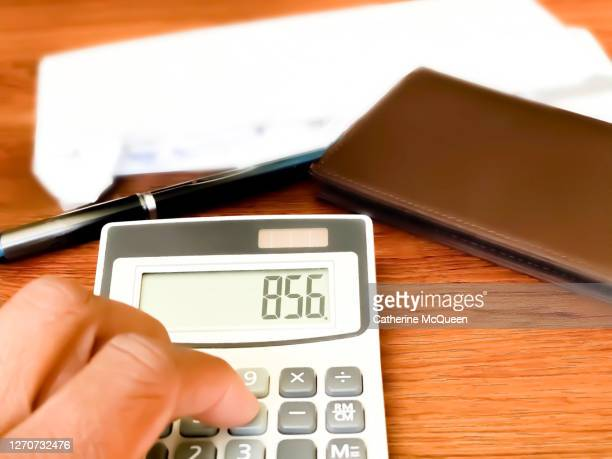 african-american female uses a calculator showing a positive balance while paying monthly bills - sociale dienst stockfoto's en -beelden