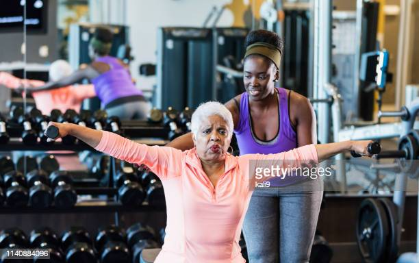 african-american fitness instructor helping senior woman - fitness instructor stock pictures, royalty-free photos & images