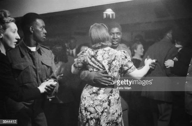 African-American GI dancing with a white girl at the Bouillabaisse Club in London's New Compton Street, Soho, 17th July 1943. Picture Post - 1486 -...