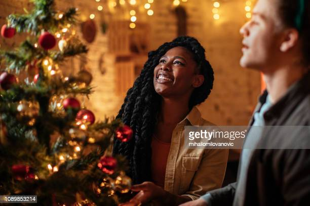 African-american girl and her boyfriend decorating Christmas tree