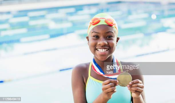 afroamerikansk flicka vid poolen, visar simma laget medalj - winners podium bildbanksfoton och bilder