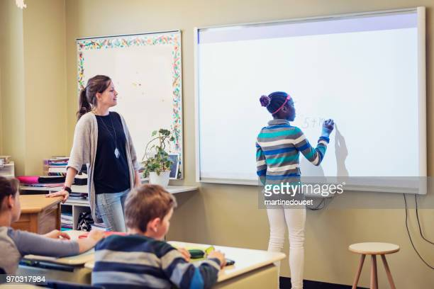 African-American girl writing on interactive whiteboard in classroom.