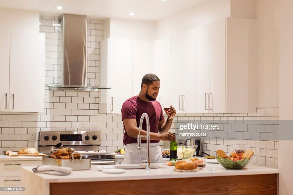 African-American having wine preparing Thanksgiving dinner. : Stock Photo