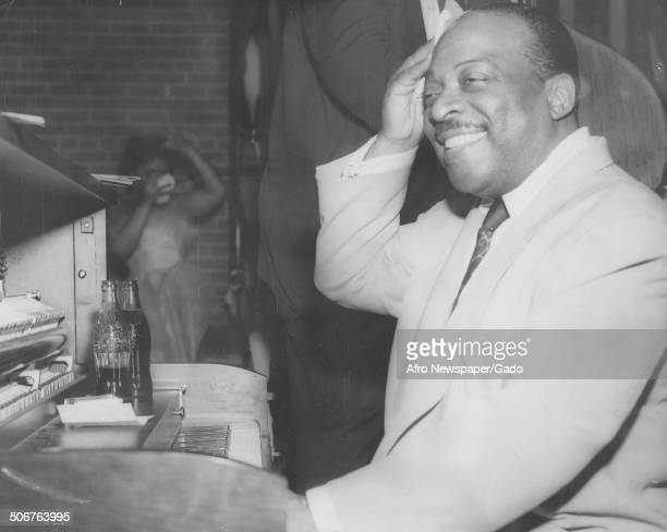 AfricanAmerican jazz musician Count Basie with Coca Cola bottles playing the piano June 1954
