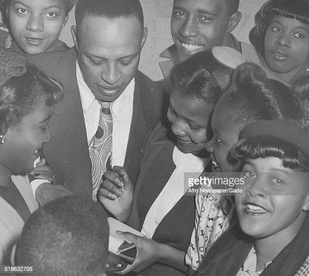 AfricanAmerican jazz vibraphonist pianist percussionist bandleader and actor Lionel Hampton signing autographs February 22 1947