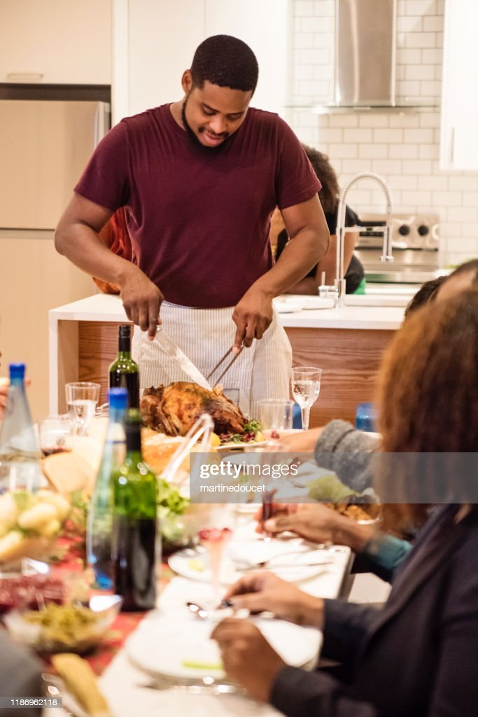 African-american man cutting turkey for Thanksgiving dinner. : Stock Photo