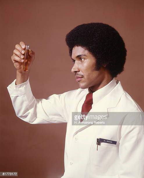 african-american man doctor chemist pharmacist scientist holding up test tube science research diagnostic. - afro amerikaanse etniciteit stockfoto's en -beelden