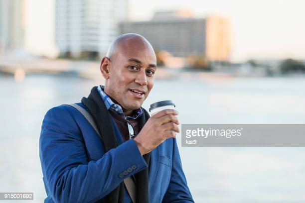 African-American man drinking coffee on city waterfront