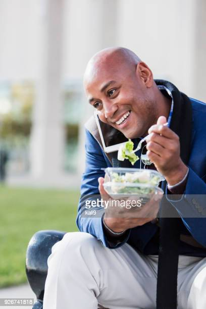 African-American man eating lunch outdoors, with phone