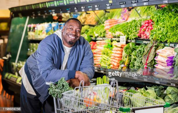 african-american man in supermarket produce aisle - fat nutrient stock pictures, royalty-free photos & images