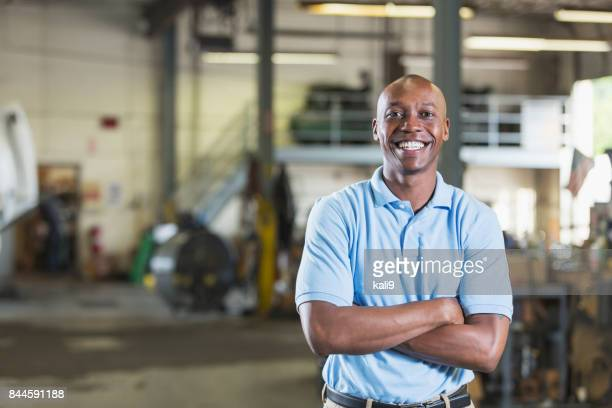 african-american man in vehicle repair shop - stereotypically working class stock pictures, royalty-free photos & images