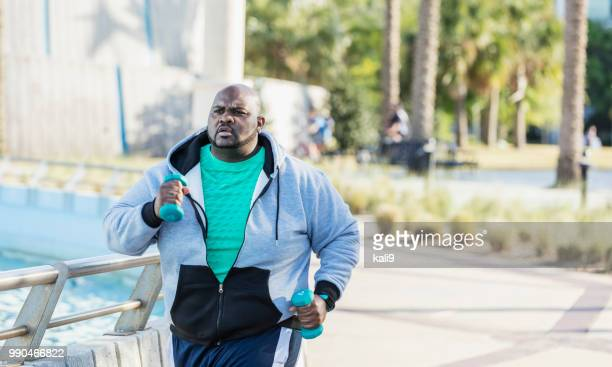 african-american man jogging or power walking - chubby men stock photos and pictures