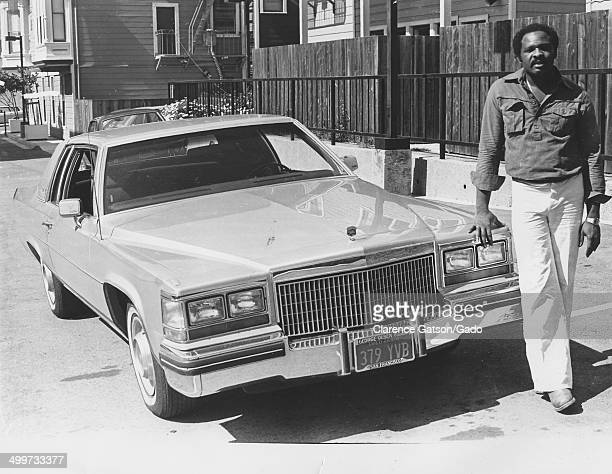 AfricanAmerican man leaning on a Cadillac automobile in an alley San Francisco California 1980
