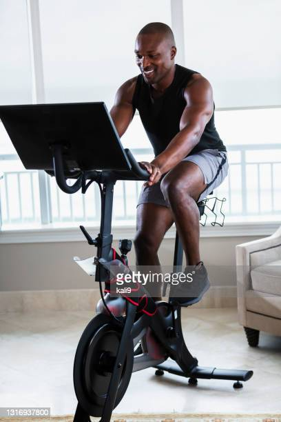 african-american man on exercise bike at home - peloton stock pictures, royalty-free photos & images