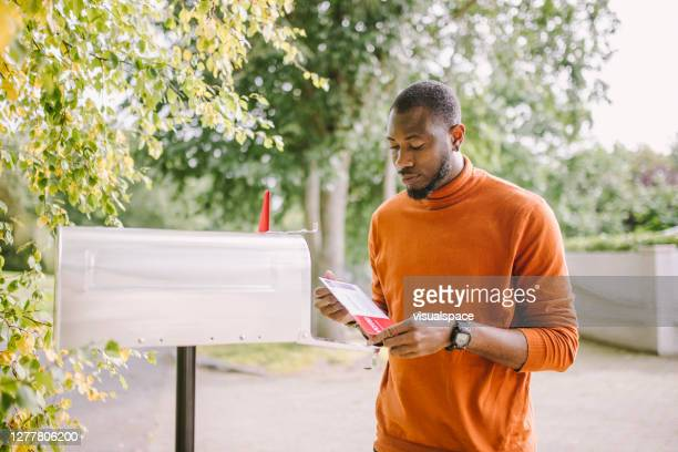 african-american man receiving voting ballot - mail stock pictures, royalty-free photos & images