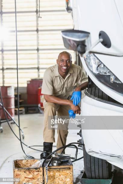 African-American man repairing semi-truck