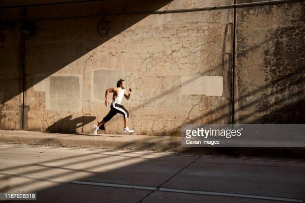 african-american man running on sidewalk - ドレッドロック ストックフォトと画像