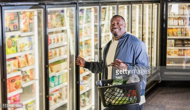 african-american man shopping for groceries - frozen food stock pictures, royalty-free photos & images